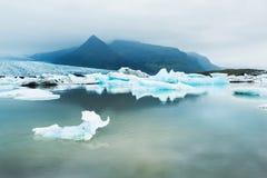 Isberg i den is- sjön med bergsikter Fotografering för Bildbyråer