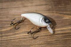 Isca de colher, atrações, moscas, equipamento para travar ou pescar um peixe predatório no fundo da madeira da plataforma fotografia de stock