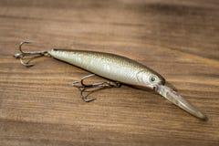 Isca de colher, atrações, moscas, equipamento para travar ou pescar um peixe predatório no fundo da madeira da plataforma fotos de stock