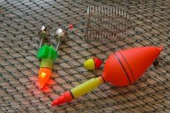 Isca, wobbler e acessórios da pesca em um fundo da rede de pesca Fotografia de Stock Royalty Free