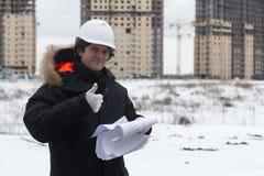 Iscensätta anseendet på bakgrunden av en ny hyreshus byggt hus Tekniker i en hjälm med legitimationshandlingar in Royaltyfria Bilder