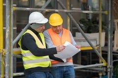 Iscensätta att ge kollegaordningar om en nybyggnadplats utomhus Arkivfoton