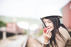 Iscensätta den asia kvinnan som kontrollerar järnvägar och, kalla radion för borgerligt och konstruktion royaltyfria foton