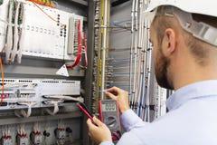 Iscensätta elektrikeren med multimeteren i elektrisk utrustning för prov för kontrollask Underhåll av den elektriska panelen arkivfoto