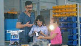 Iscensätta och två scgoolbarn som återmontera en quadcopter Innovation i utbildningsbegrepp stock video
