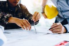 Iscensätta partnerskap som arbetar med ritningar och tillsammans diskuterar projekt på mötet i kontoret arkivfoto