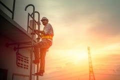 Iscensätta teknikeren som arbetar på stegen för att fixa elektricitetskabel royaltyfri bild