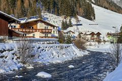 Small mountain stream in Tyrol Alps. Wooden house is near mountain river is covered by snow Stock Image