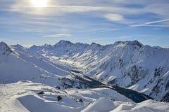 Ischgl bergpanorama - solig vinterdag i Tyrol fjällängar: dolda berglutningar för snö och blå himmel Arkivfoton