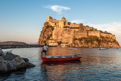 Ischi, Italia 20 giugno 2017: Barcaiolo con una barca sui precedenti del castello aragonese fotografia stock libera da diritti