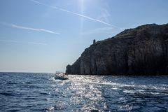 Ischia fartyg som går in mot solnedgången royaltyfri fotografi