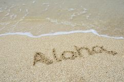 Iscrizione aloha sulla sabbia alla spiaggia. Fotografie Stock