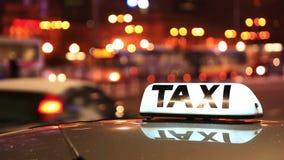Iscrizione brillante del taxi contro passare le automobili sulla via di notte della città video d archivio