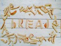 iscrizione dai pezzi di cracker bianchi su un fondo bianco Fotografia Stock Libera da Diritti
