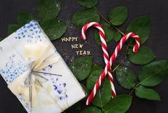 Iscrizione del nuovo anno su un bordo nero con il regalo e la caramella rossa Fotografie Stock Libere da Diritti