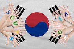 Iscrizione della Corea del Sud sulle mani dei bambini contro lo sfondo di una bandiera d'ondeggiamento della Corea del Sud fotografia stock