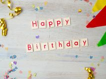 Iscrizione di buon compleanno con la decorazione del partito su fondo di legno