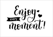 Iscrizione di calligrafia Enjoy ogni momento! decorato con i cuori ed il nastro Fotografie Stock