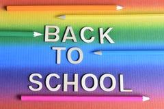 Iscrizione di nuovo alla scuola con i pastelli sui precedenti dell'arcobaleno immagini stock