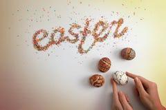 Iscrizione di Pasqua fatta dal suga variopinto di cottura e dalle mani femminili che tengono uovo variopinto Immagine Stock Libera da Diritti