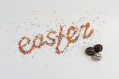 Iscrizione di Pasqua fatta dalle caramelle variopinte dello zucchero e di cioccolato di cottura sopra fondo variopinto con lo spa Fotografia Stock Libera da Diritti