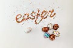 Iscrizione di Pasqua fatta dallo zucchero variopinto di cottura e dalle uova disegnate a mano variopinte Immagine Stock Libera da Diritti