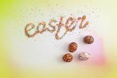 Iscrizione di Pasqua fatta dallo zucchero variopinto di cottura e dalle uova disegnate a mano variopinte Immagine Stock
