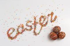 Iscrizione di Pasqua fatta dallo zucchero variopinto di cottura e dalle uova disegnate a mano variopinte Immagini Stock Libere da Diritti