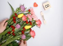 Iscrizione l'8 marzo con i fiori su un fondo bianco Fotografie Stock