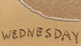 Iscrizione MERCOLEDÌ su una sabbia delicata della spiaggia con l'onda molle Fotografia Stock