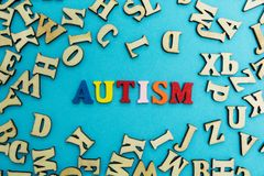 """Iscrizione multicolore """"autismo """"su un fondo blu, lettere sparse fotografie stock"""