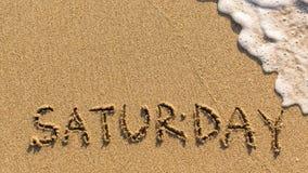 Iscrizione SABATO su una sabbia delicata della spiaggia con l'onda molle Fotografia Stock Libera da Diritti