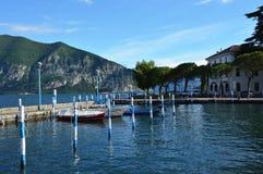 ISEO ITALIEN - MAJ 13, 2017: Sikt av pir av Iseo sjön med fartyg, Iseo, Italien Arkivbild