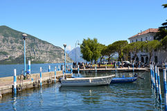 ISEO ITALIEN - MAJ 13, 2017: Sikt av pir av Iseo sjön med fartyg, Iseo, Italien Royaltyfri Bild