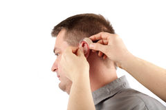 Iserting a hearing aid. Audiologist inserting a hearing aid into a middle-aged man's ear - isolated on white Royalty Free Stock Photos