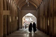 ISFAHAN, DER IRAN - 20. AUGUST 2016: Frauen, die den islamischen Schleier geht in eine Straße des bedeckten Basars von Isfahan tr Lizenzfreies Stockbild