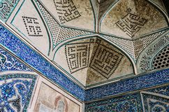 Arabic Quranic calligraphy witten in Thuluth script on polychrome tiles, on the corner of the Imam Mosque. Isfahan, Iran - April 22, 2018: Arabic Quranic Royalty Free Stock Image