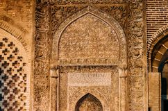 Arabic Quranic calligraphy witten in Thuluth script on the side of a wall, at the Imam Mosque royalty free stock photography