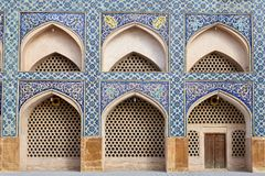 Arches in the wall in the Jame Mosque, Isfahan, Iran. Isfahan, Iran - April 24, 2017: Arches in the mosaic wall in the Iranian Jame Mosque Stock Photography