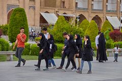 Boys and girls are talking on the go, Isfahan, Iran. Isfahan, Iran - April 24, 2017: Group of boy and girl, college age, walk along Imam Square, and chat gaily Royalty Free Stock Images