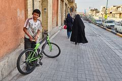 Iranian boy is standing on the street, Isfahan, Iran. Isfahan, Iran - April 24, 2017: an Iranian boy with a bicycle is standing on the street, along which women Royalty Free Stock Photography