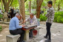 Elderly Iranians play chess in the park, Isfahan, Iran. Isfahan, Iran - April 24, 2017: The old people are playing chess in the city park royalty free stock images