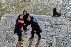 Iranian schoolgirls do selfie photo shoot near river, Isfahan, I royalty free stock photography