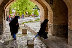 Iranian girls step over flow of water under bridge, Isfahan. Isfahan, Iran - April 24, 2017: Two Iranian girls dressed in a black Muslim chador are crossing the stock photo