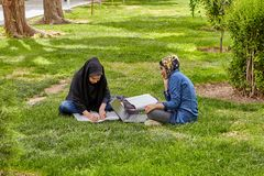 Girls are preparing for classes on lawn in park, Iran. Isfahan, Iran - April 24, 2017: Two Muslim female students, dressed in Islamic hijab, are preparing for stock image