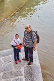 Father and daughter are standing by the river, Isfahan, Iran. Isfahan, Iran - April 24, 2017: Two-person family, mature adult man and small school-age girl Stock Image
