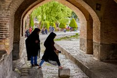 Young iranian women jump over water under bridge, Isfahan, Iran. Isfahan, Iran - April 24, 2017: Two young Iranian Muslim women, dressed in a black islamic royalty free stock images