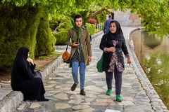 Young Muslim women in hijabs, walking in park near river. royalty free stock photo