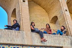 Young people rest in arched niches of bridge, Isfahan, Iran. Isfahan, Iran - April 24, 2017: A young man talks to the girls, sitting on an arched niche of a Royalty Free Stock Image