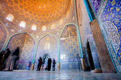 ISFAHAN, IRAN - OCT 14: Tourists inside fantastic designed mosque with tiled dome and walls Stock Images